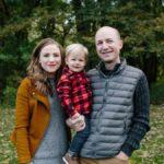 family of three posing outdoors