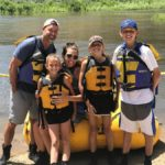 family wearing life jackets posing near water