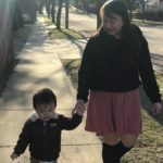 woman and child holding hands walking on sidewalk