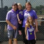 family posing outdoors in front of a fence